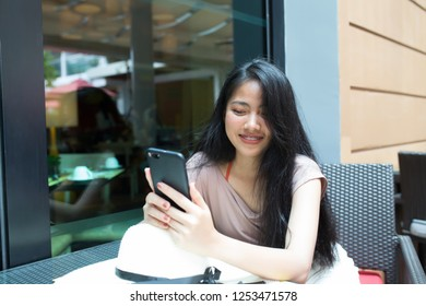Happy asian woman holding smart phone in coffee shop