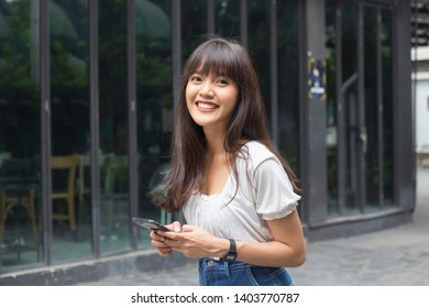 Happy asian woman holding smart phone in front of restaurant
