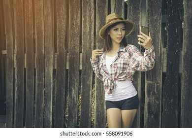 Happy asian woman holding smartphone, leaning against old wooden barn wall, vintage retro color style.