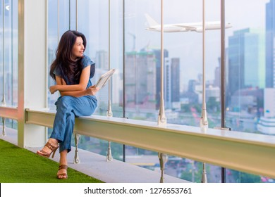 Happy asian woman holding tablet computer and looking away at copy space while sitting near window glass with airplane and business buildings on background.