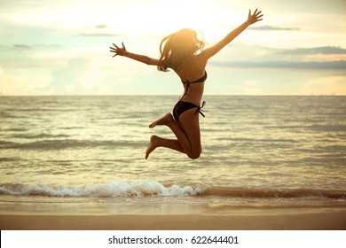 Happy Asian woman jumping on the beach. Summer vacation concept,Sunset ,hight key.
