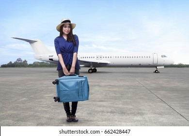 Happy asian woman passenger wearing hat holding suitcase waiting airplane to take off