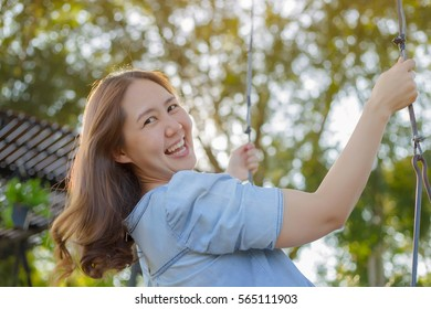 Happy Asian woman playing swing outdoor in the park