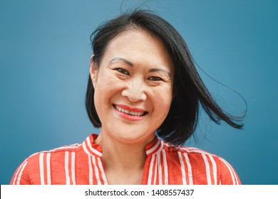 Happy Asian woman portrait against blue background - Senior Chinese female having fun posing in front of camera - Concept of elderly with old generation lifestyle