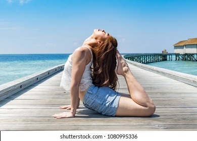 Happy Asian woman practice yoga king cobra or Raja Bhudjangasana pose to stretching her muscle on wooden bridge on the beach in Maldives,Feeling so comfortable and relax in holiday,Healthy Concept