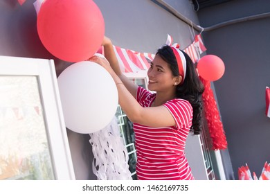 happy asian woman preparing for indonesia independence day decorating her house