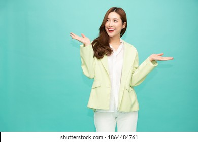 Happy Asian woman presenting or showing open hand palm with copy space for product isolated over green background