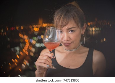 Happy asian woman with red cocktail in black dress, background is night city have bokeh