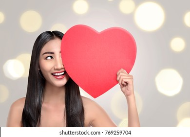 Happy asian woman with red heart in hand against blur light background