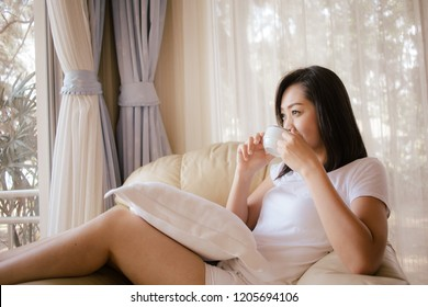 Happy asian woman relax with coffee and morning light in living room.