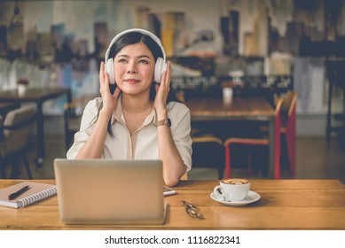 Happy Asian woman relaxing and listening music in coffee shop with computer laptop and coffee cup. People and lifestyles concept. Freelance and outdoors workplace outdoors theme.