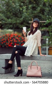 Happy asian woman resting with coffee cup in the city. Happy lovely and beautiful mixed race Asian Caucasian young girl in casual clothes with cap and handbag outdoor sitting on bench on the city