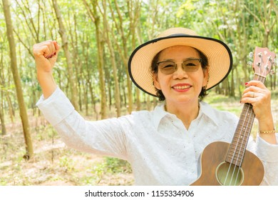 Happy asian woman senior aging old adult confident cheerful in park outdoors smile to passive income freedom success from retirement financial investment plan. Good care of wealth and health lifestyle