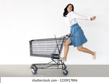 happy asian woman with shopping cart ready for shopping on sale season - Beautiful casual shopper girl going to the store.