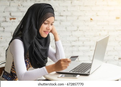 Happy asian woman shopping online with credit card and computer.Internet shopping.