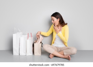 Happy asian woman shopping online at home sitting besides row of shopping bags