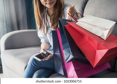 Happy asian woman sitting on sofa and using smart phone for shopping online payment and colourful shopping bags, Online shopping concept