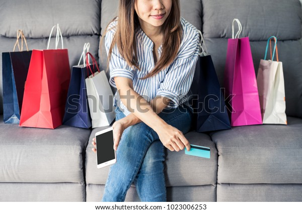 Happy asian woman sitting on sofa and holding credit card and smart phone for shopping online payment and colourful shopping bags, Online shopping concept