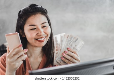 happy Asian woman with smart phone and banknotes in hand ,make money online concept