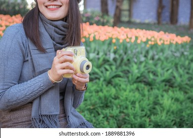 Happy Asian woman smiling  in woolen grey cap holding and using Polaroid camera in garden.