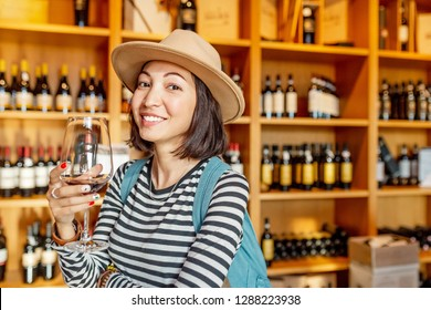 Happy asian Woman sniffing and tasting red wine in a glass in winery shop