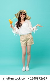 Happy Asian woman in summer casual clothes holding a glass of fruit juice drink studio shot isolated on light blue backgroud