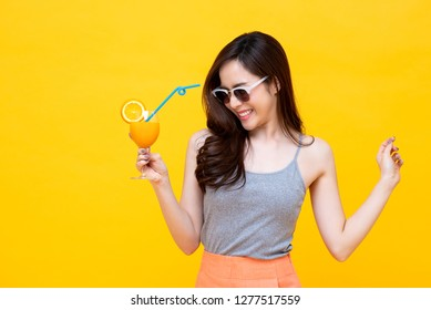 Happy Asian woman in summer casual clothes with a glass of fresh fruit juice drink studio shot isolated on colorful yellow backgroud