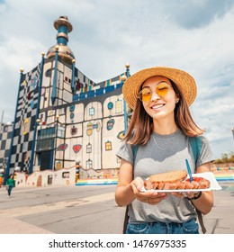 Happy asian woman tasting austrian delicious sausages wurst in Vienna