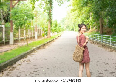 Happy Asian woman teenage in casual dress walk with big smaile in outdoor park with copy space.