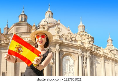 Happy Asian woman traveler stands with the Spanish flag on the main square of Zaragoza against the background of the Basilica Del Pilar