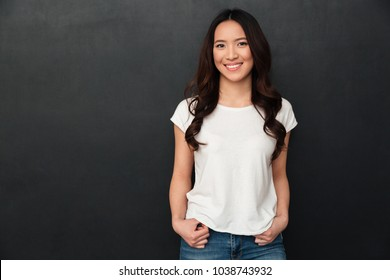 Happy asian woman in t-shirt posing and looking at the camera over black background