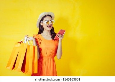 Happy Asian woman using cell phone on yellow background, autumn season,colorful shopping concept.
