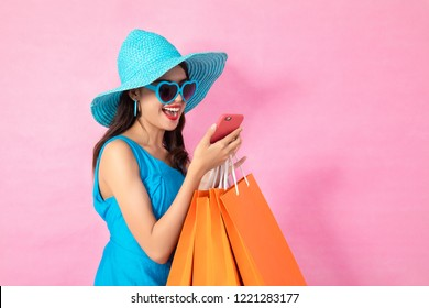 Happy Asian woman using cell phone on Pink background, colorful shopping concept.