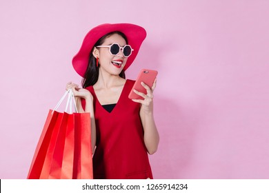 Happy Asian woman using cell phone on pink background, christmas theme season,colorful shopping concept.