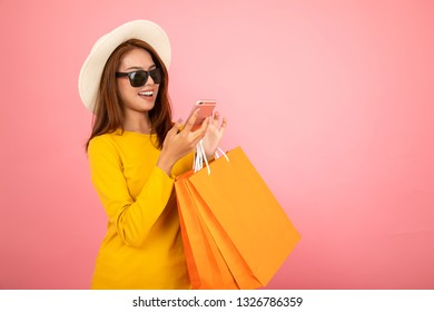 Happy Asian woman using cell phone on yellow background, summer season,colorful shopping concept.