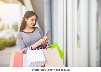 Happy Asian woman using cell phone at a shopping center
