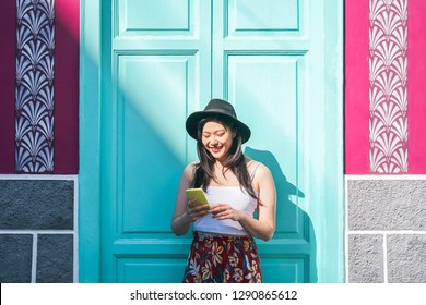 Happy asian woman using mobile smart phone outdoor - Chinese fashion girl watching on new trends social networks - Web influencer, millennials, technology and generation z concept