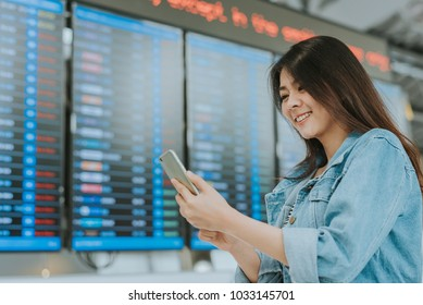 Happy asian woman using smartphone at airport with flight information board in background