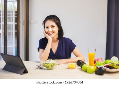 Happy Asian woman vegetarian healthy eating salad food and use tablet on the table. Young woman vegetarian. Vegetables and fruits. Vegan food.