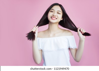 A happy asian woman is very satisfied with her appearance. Young and healthy, healthy hair and skin. Cheer and crimson on a pink background. Enjoy life and smile, friendly, sweet and beautiful