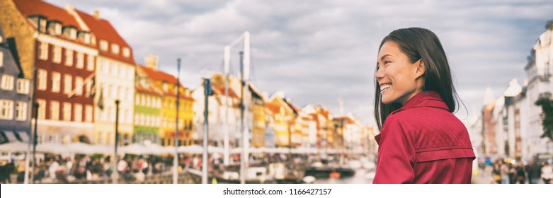 Happy Asian woman walking in Copenhagen city street. Denmark spring travel tourist visiting Nyhavn famous attraction, old water canal banner.