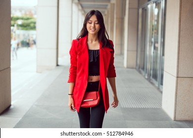 Happy asian woman walking outdoors in business casual red suite against mall