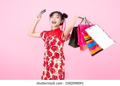 Happy Asian woman wearing cheongsam traditional red dress for Chinese new year day holding shopping bags and credit card on pink.