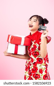 Happy Asian woman wearing cheongsam traditional red dress for Chinese new year day holding gift boxes and credit card on pink.