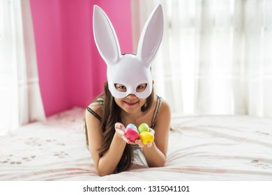 Happy Asian woman in white mask Easter bunny on bed hold paint colorful Easter eggs on hands. Funny face. Happy easter. Fashion portrait of beautiful sensual woman