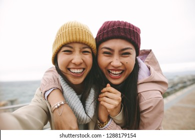 Happy asian woman in winter wear standing near the sea on a cold morning. Smiling women standing outdoors holding each other and having fun on a winter morning.