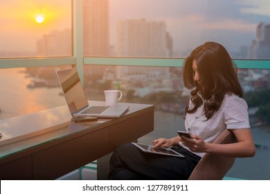 Happy asian woman working using multiple devices on a desk while sitting at office and Business buildings, River, Beautiful sun on background.