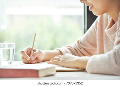 Happy Asian woman writing in notebook or diary or paperwork on white desk at the house. Smiling Thai Girl relaxing on holiday. Copy space.