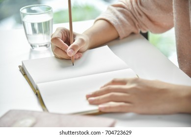 Happy Asian woman writing on notebook or diary with white desk in bedroom. Copy space.