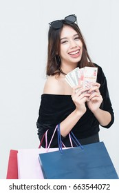 Happy Asian women with shopping bag and holding money